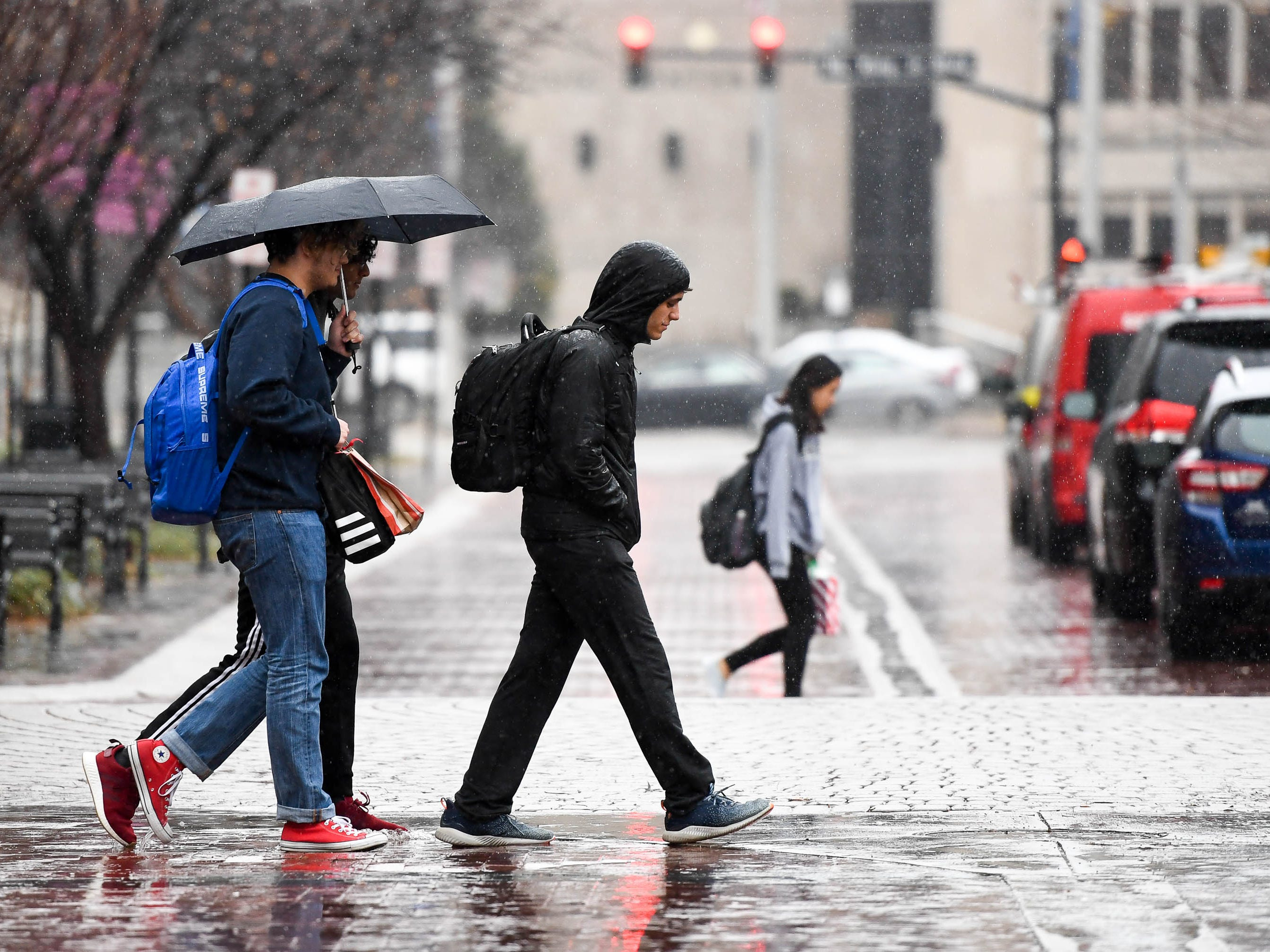 Moving between classes, Signature School students cross Main Street in the rain as showers move through the Evansville area Thursday, December 13, 2018.