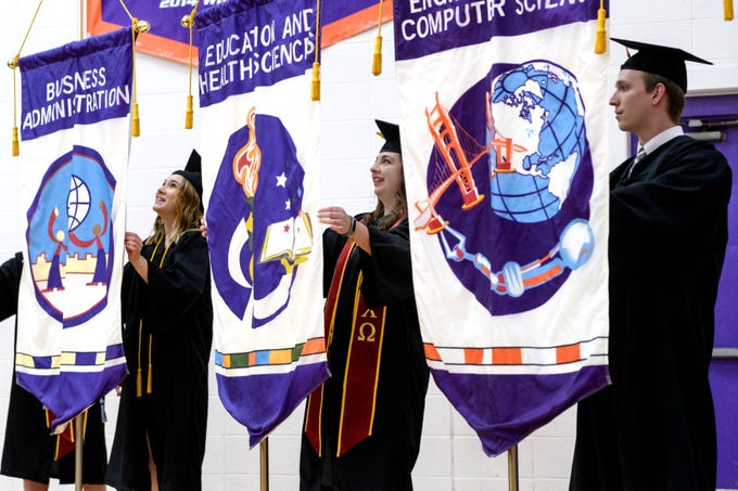 University of Evansville graduates Sierra Voegerl, from left, Lindsey Mayper and Chris Johnson present flags that represent the university's academic colleges and schools alongside Kathryn Hannon and Malia Borowiak, both not pictured, during the winter commencement ceremony held at Meeks Family Fieldhouse inside UE's Carson Center in Evansville, Ind., Thursday, Dec. 13, 2018. More than 40 students participated in the commencement ceremony.