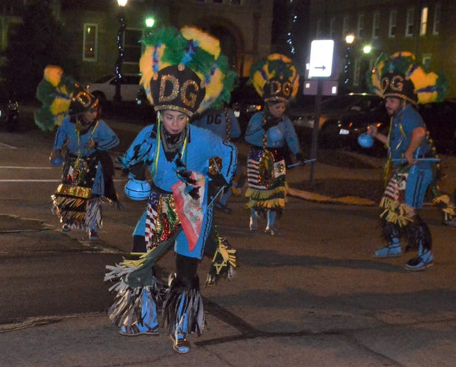 Members of Danza Guadalupana, based in Norwalk, dance down Croghan Street on their way to St. Joseph Catholic Church on Wednesday night to celebrate Our Lady of Guadalupe.