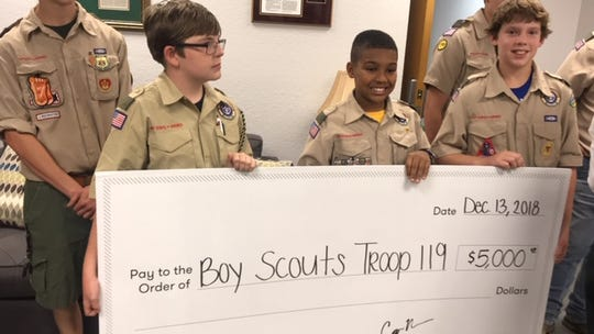 Members of Boy Scout Troop 119, from right, Jack Boldrin, Royce Bynum and John Kelly, hold a replica of a check for $5,000 that Lee County Sheriff Carmine Marceno presented them Thursday to help their 2019 camping experience that was imperiled due to a lack of Christmas trees to sell this year.