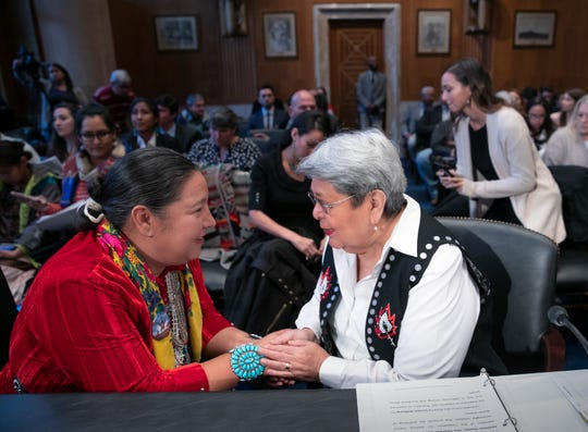 Amber Crotty from Window Rock, Ariz., left, a delegate of the Navajo Nation Council, and Patricia Alexander of the Tlingit and Haida Indian Tribes of Alaska, right, exchange words of encouragement to each other before testifying as the Senate Committee on Indian Affairs holds a hearing to examine concerns about investigations into the deaths and disappearance of Native American women, on Capitol Hill in Washington, Wednesday, Dec. 12, 2018.