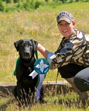 Michaela Hystad and Teal pose with a hunting retriever club hunt test trial award.