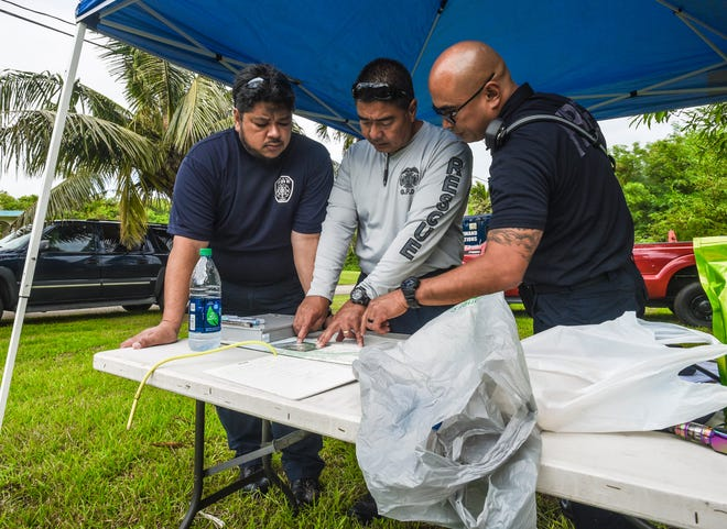 Guam Fire Department look over maps to coordinate search efforts for a missing crab hunter, at an incident command post along Chalan Asiga in Malojloj, on Thursday, Dec. 13, 2018. Michael Guerrero, 45, was reported missing after he got separate from others in a hunting party who set on their hunt during the early morning hours the previous day, according to Guam Fire Department firefighter and spokesman Kevin Reilly. The search was initiated for the man after a call was received by GFD at about 4:00 p.m. Wednesday which continued throughout the night and into Thursday morning, Reilly added.