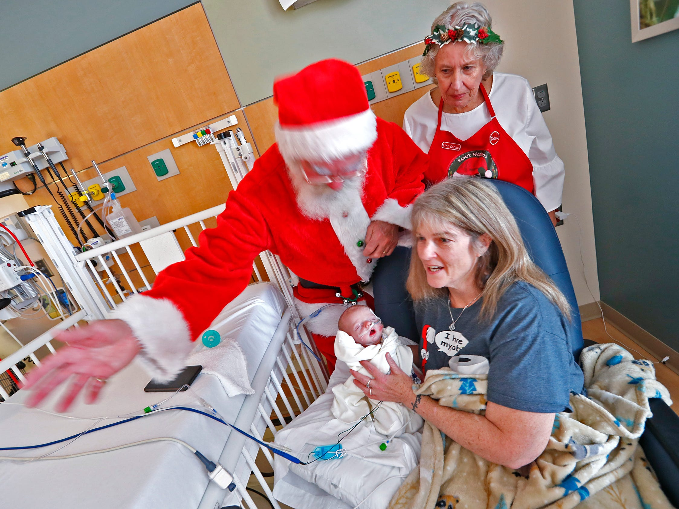 Santa and Mrs. Claus, aka Bill and Kathy Armstrong, talk with Patty Fultz and her grandson Jasper Butler, while the Clauses visit with kids at Riley Children's Health, Thursday, Dec. 13, 2018.