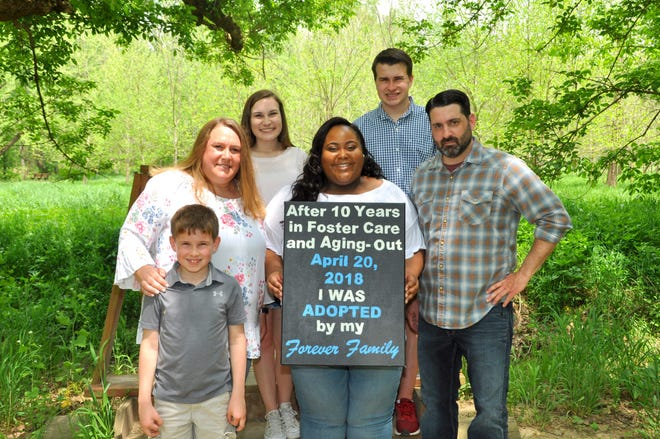 Shay Roberson-Wing, 24, was adopted in 2018 by her former school resource officer, Ginnie Wing, and Wing's husband Matt. The family posed for a photo.