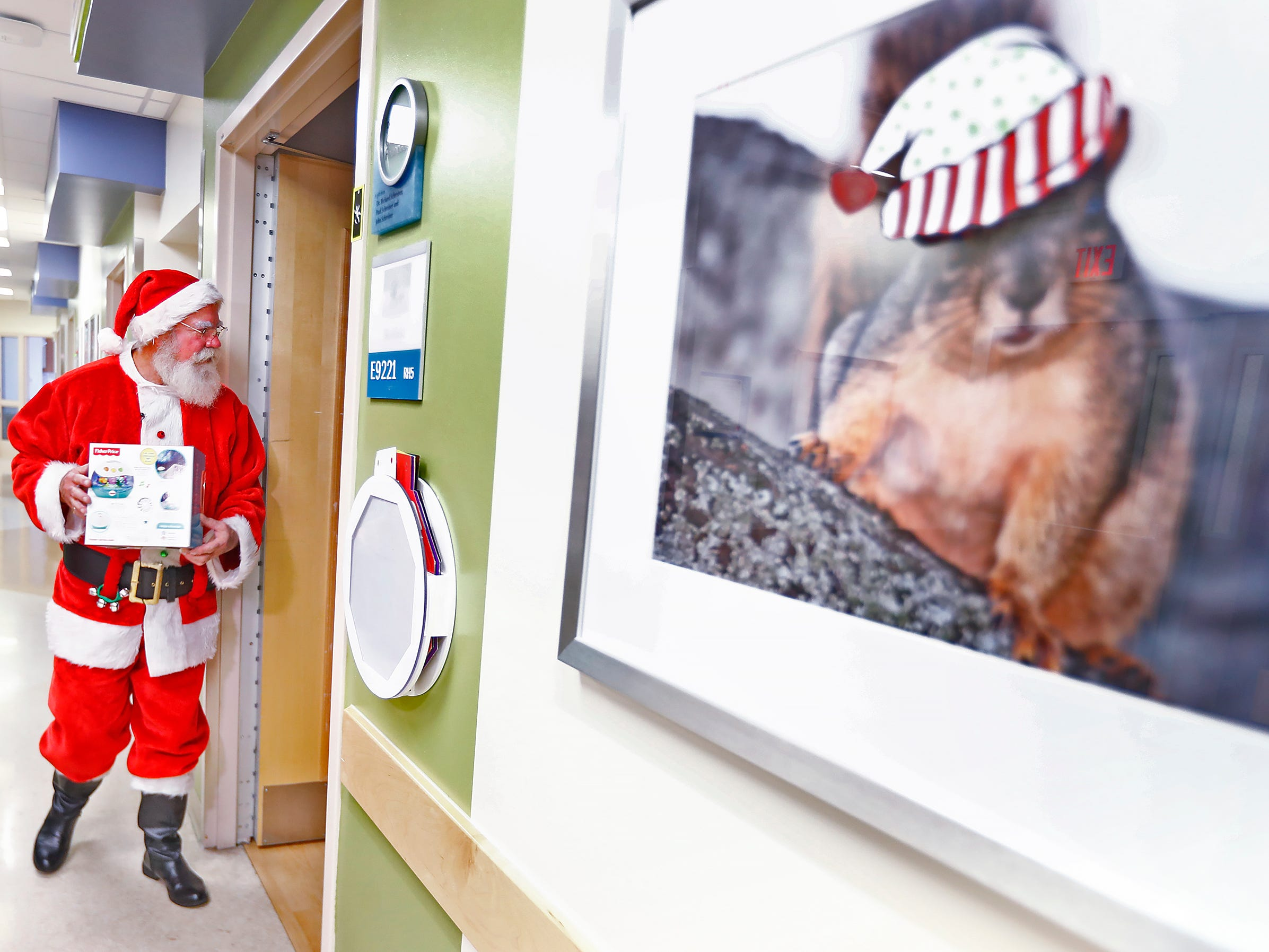 Santa Claus, aka Bill Armstrong, gets ready to walk into a patient's room, as he and Mrs. Claus, Kathy Armstrong, visit with kids at Riley Children's Health, Thursday, Dec. 13, 2018.