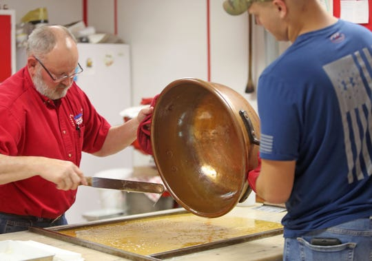 John Badger XIV pours the sugar mixture with the help of grandson Grandson John XVI at the Martinsville Candy Kitchen, Wednesday, Dec. 12, 2018.
