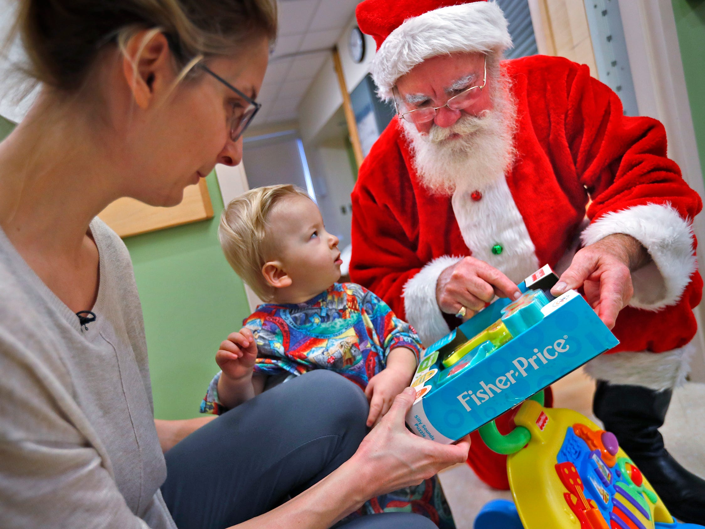 Finnick McCandless, center, sits with his mother, Celena McCandless, left, as they visit with Santa Claus, also know as Bill Armstrong, during Santa's visit with kids at Riley Children's Health, Thursday, Dec. 13, 2018.