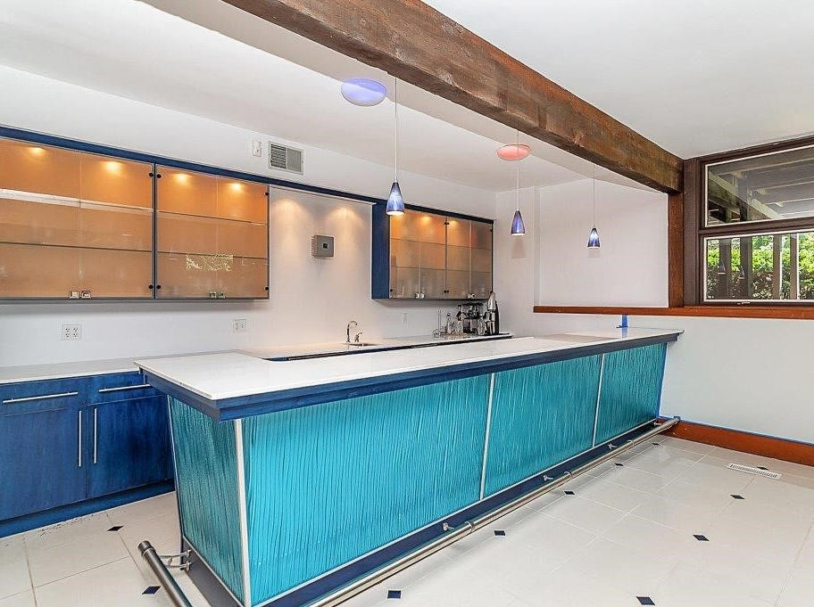 The basement includes an entertainment area with a vibrant, blue bar and a theater room.