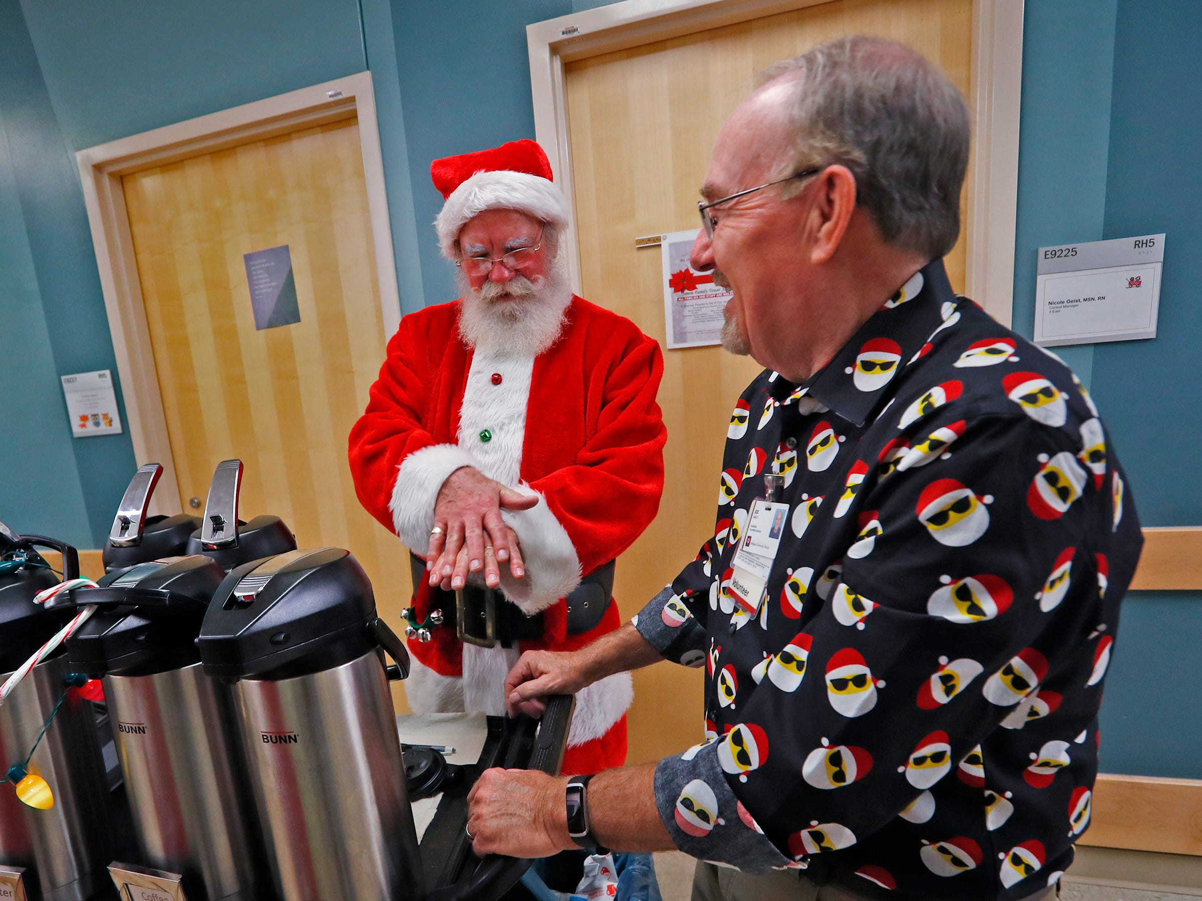 Santa, aka Bill Armstrong, jokes about how to wash hands with volunteer Joe Gault, while Santa and Mrs. Claus visit with kids at Riley Children's Health, Thursday, Dec. 13, 2018.
