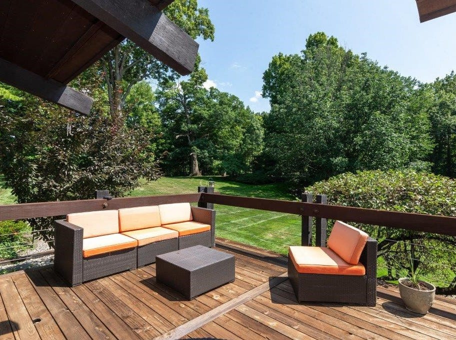 A deck extends the length of the home  with cooking and seating areas.