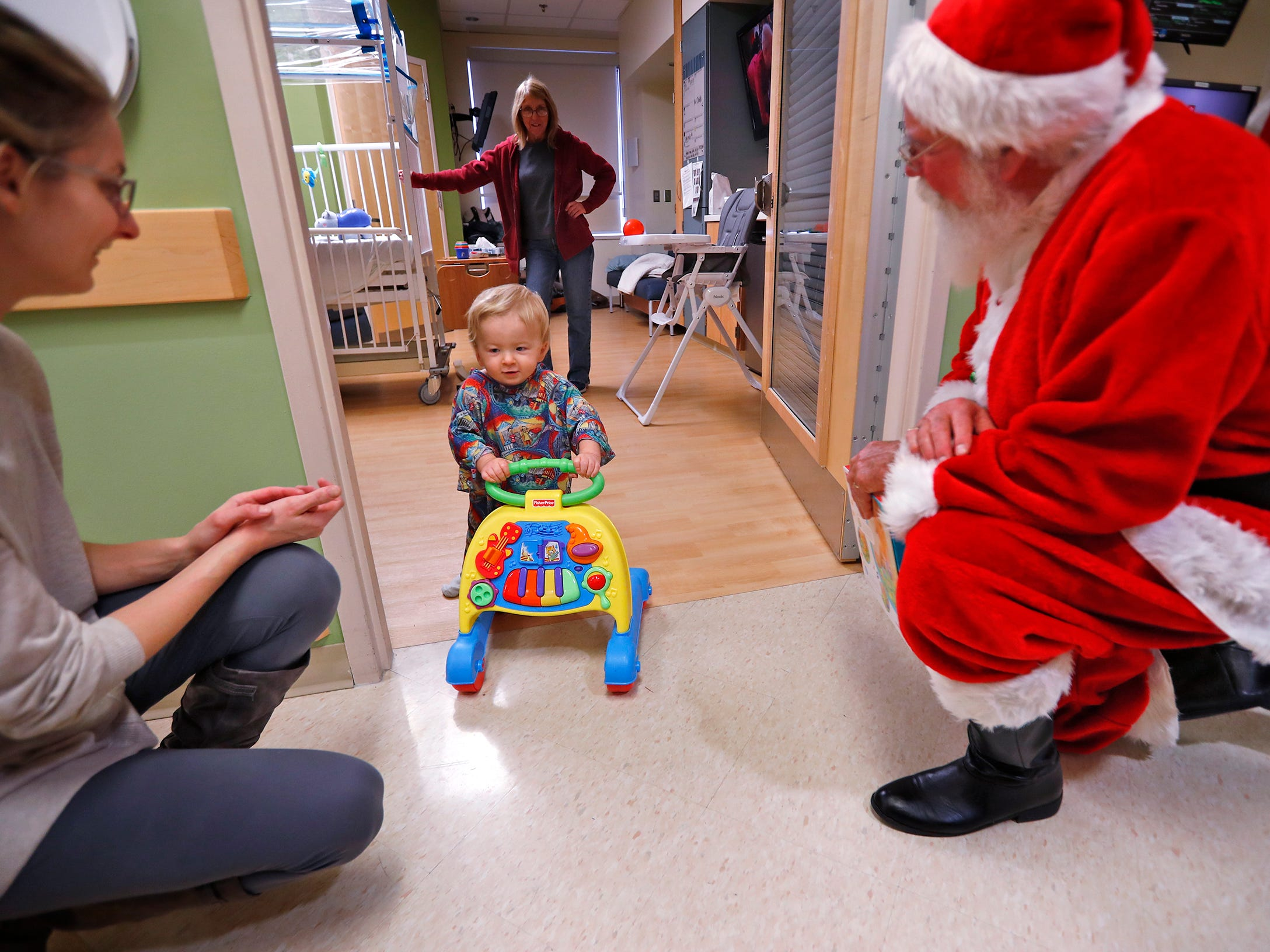 Finnick McCandless, center, walks out to his mother, Celena McCandless, left, and Santa, also know as Bill Armstrong, during Santa's visit with kids at Riley Children's Health, Thursday, Dec. 13, 2018.
