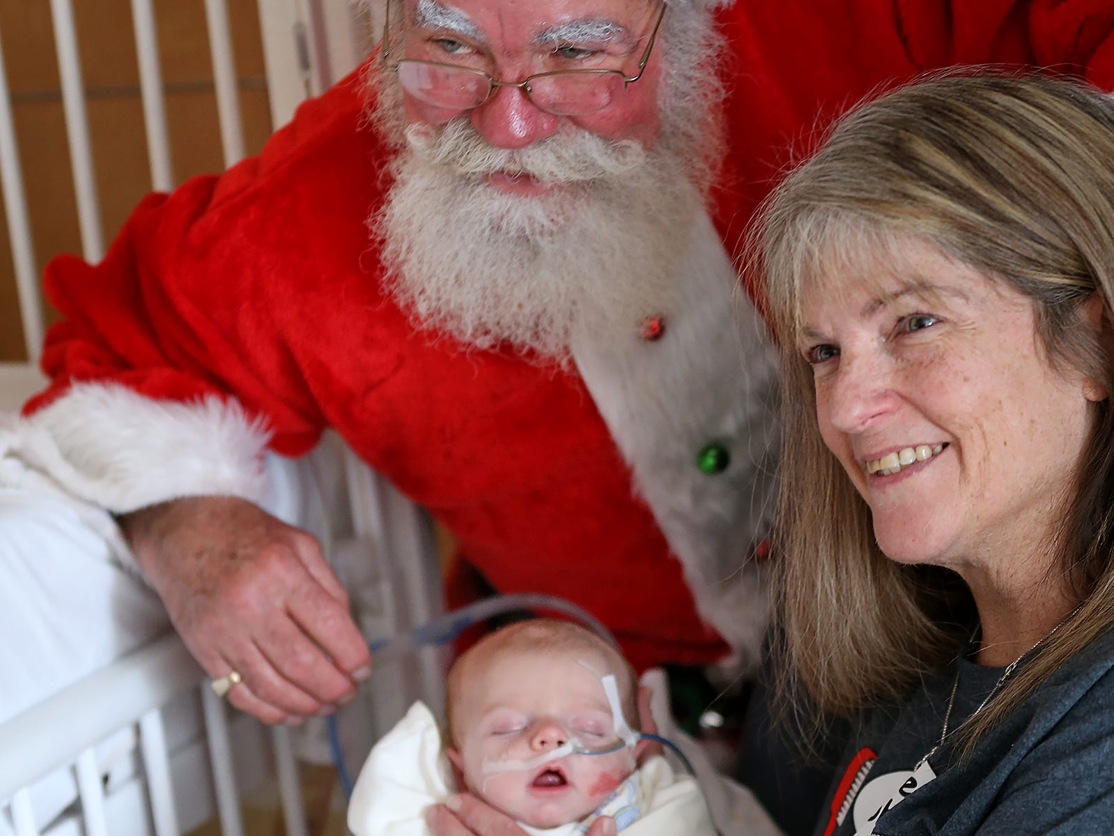 Santa, aka Bill Armstrong, poses for a photo with Patty Fultz and her grandson Jasper Butler, while the Clauses visit with kids at Riley Children's Health, Thursday, Dec. 13, 2018.