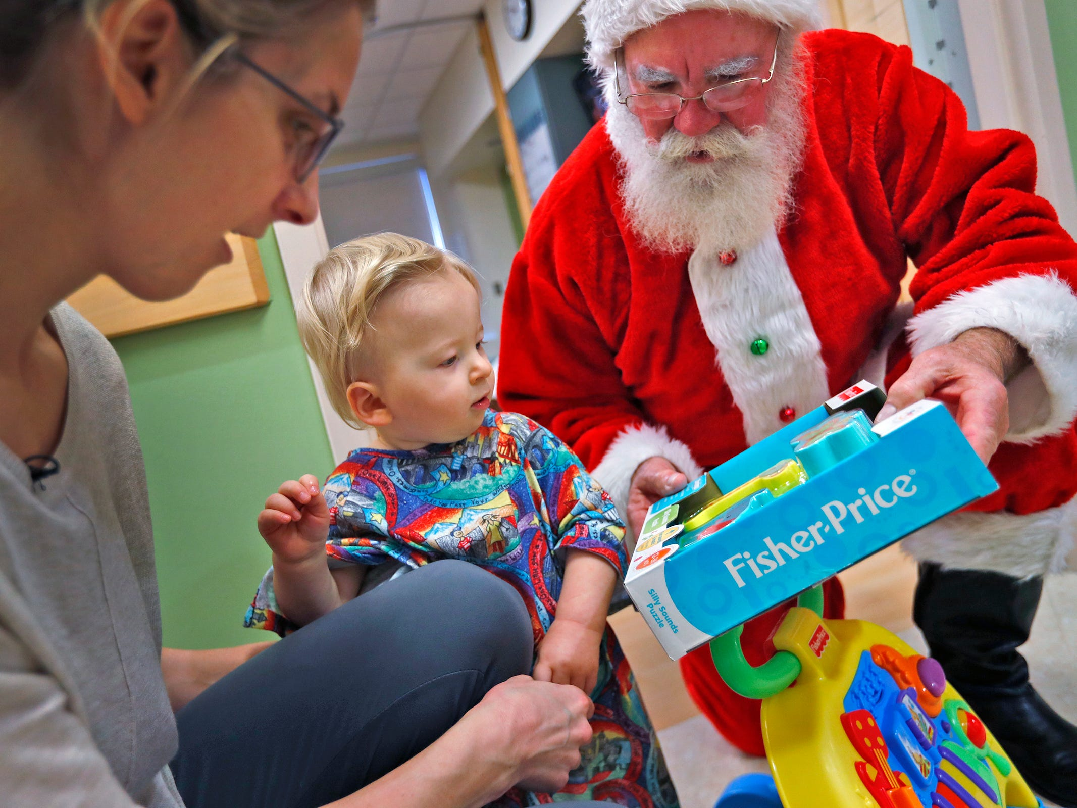 Finnick McCandless, center, sits with his mother, Celena McCandless, left, as they visit with Santa, also know as Bill Armstrong, during Santa's visit with kids at Riley Children's Health, Thursday, Dec. 13, 2018.