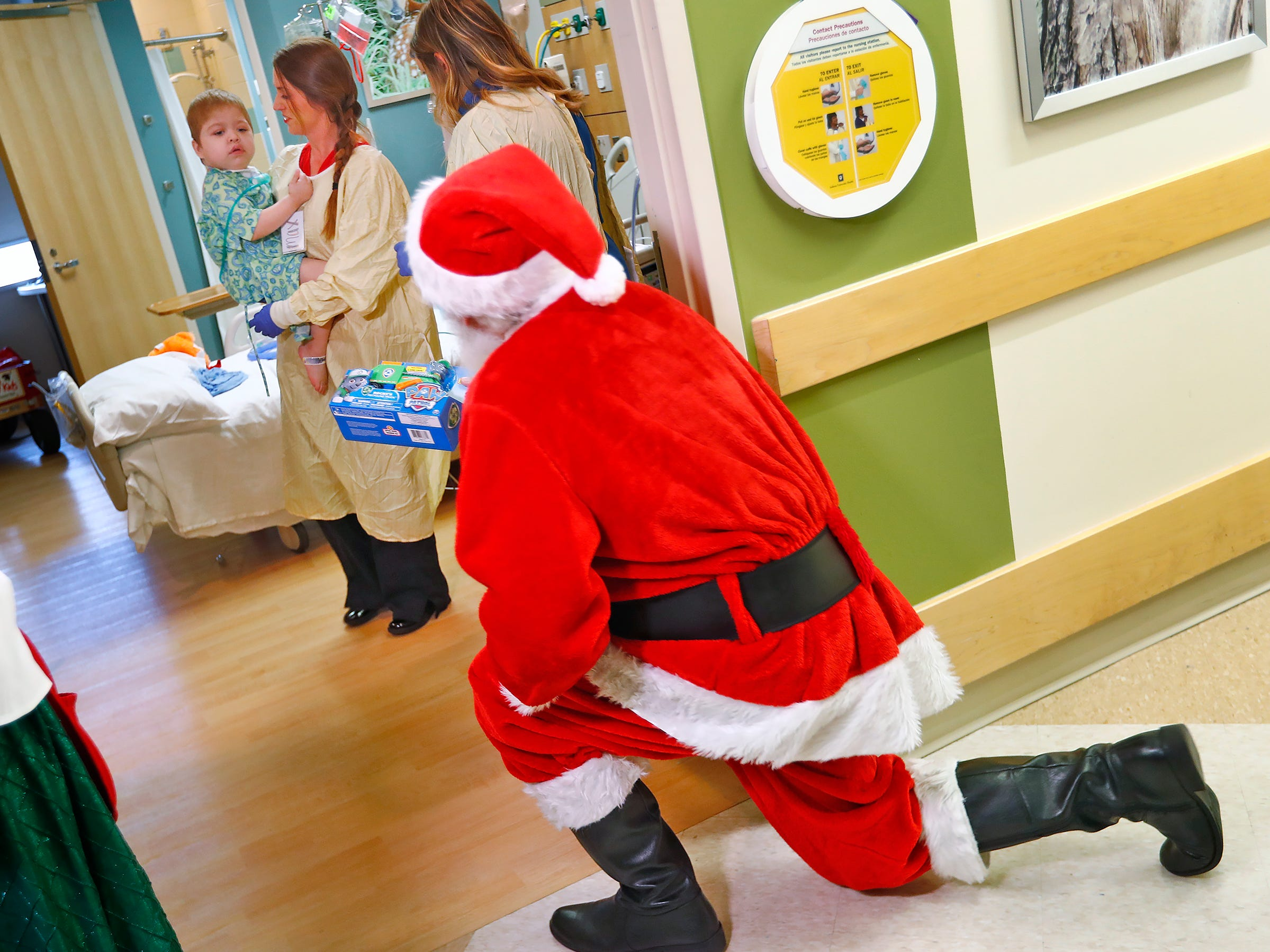 Kristen Cote, RN, center, and Child Life Specialist Meg Sanders, bring Max Goodman out to visit with Santa and Mrs. Claus, aka Bill and Kathy Armstrong, at Riley Children's Health, Thursday, Dec. 13, 2018.