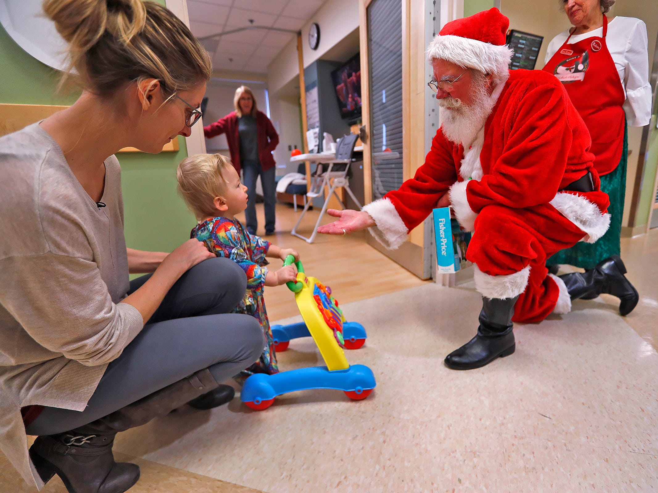 Finnick McCandless, center, sits with his mother, Celena McCandless, left, as they visit with Santa and Mrs. Claus, also know as Bill and Kathy Armstrong, during Santa's visit with kids at Riley Children's Health, Thursday, Dec. 13, 2018.
