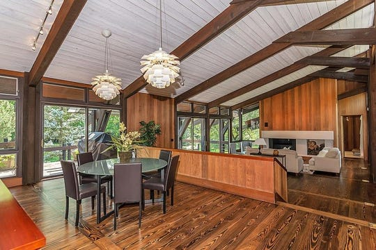 Inside, the dining room overlooks the open living area. Floor-to-ceiling windowed doors open out to a large deck and view of the surrounding trees.