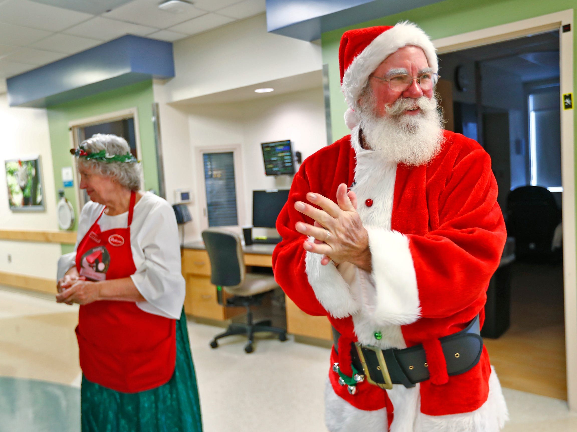 Santa and Mrs. Claus, aka Bill and Kathy Armstrong, prepare to go into another child's hospital room as they visit with kids at Riley Children's Health, Thursday, Dec. 13, 2018.