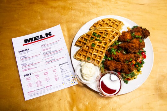 A plate of chicken and waffles is seen on Thursday, Dec. 13, 2018, at Melk in Iowa City. The chicken is breaded in Cap'n Crunch cereal and served with Sriracha maple syrup on a bed sautéed greens.