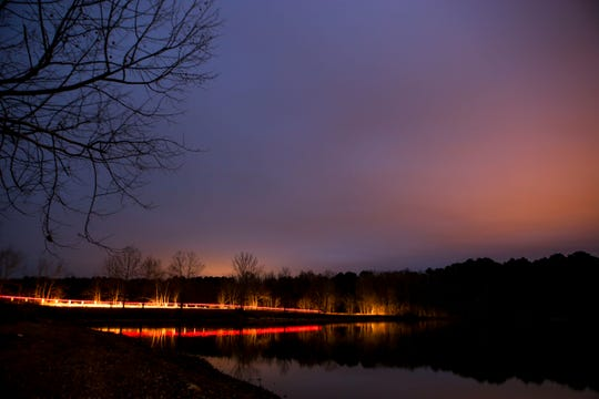 In this long exposure photo, a car can be seen driving along Black Bottom Road passing Beech Lake in Lexington, Tenn., on Wednesday, Dec. 12, 2018.