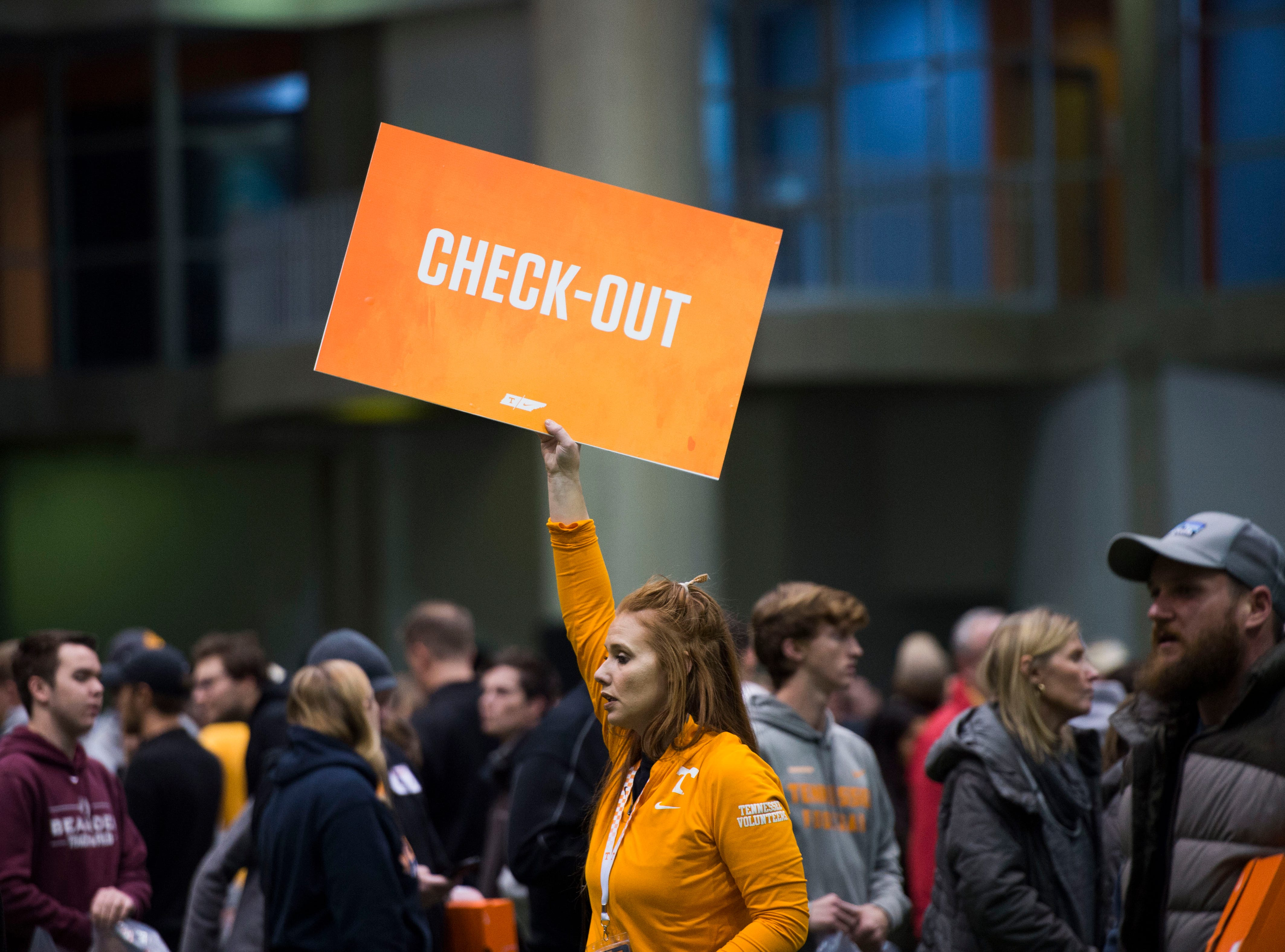 An assistant holds a line marking the check-out area as people shop for athletic apparel on Tennessee football's indoor practice field during University of Tennessee Athletic Department's inventory sale Wednesday, Dec. 12, 2018. Helmets and jerseys were sold along side the discount gear for hundreds of dollars.