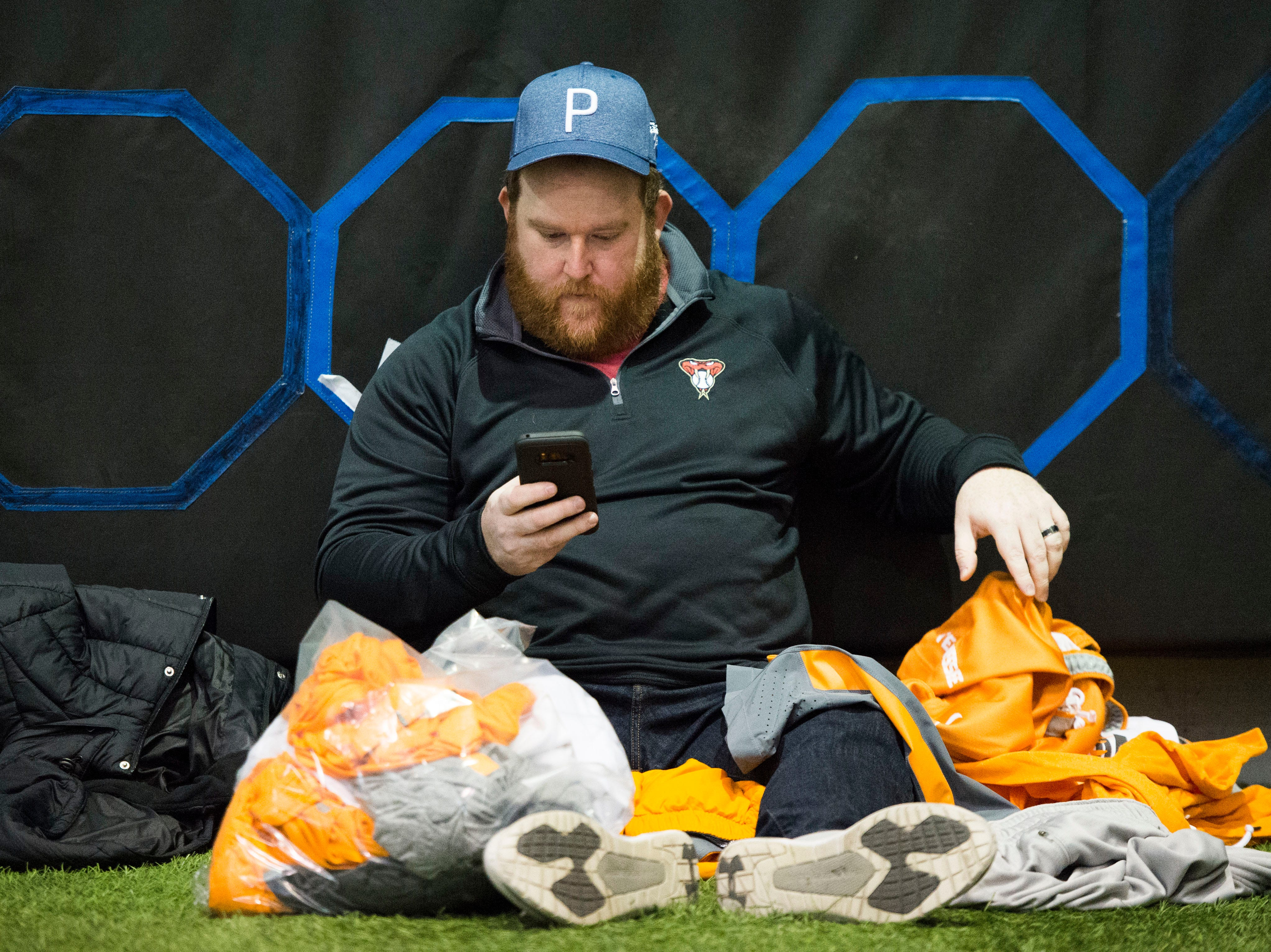 Daniel Howard of Knoxville takes a break from shopping for athletic apparel on Tennessee football's indoor practice field during University of Tennessee Athletic Department's inventory sale Wednesday, Dec. 12, 2018. Helmets and jerseys were sold along side the discount gear for hundreds of dollars.