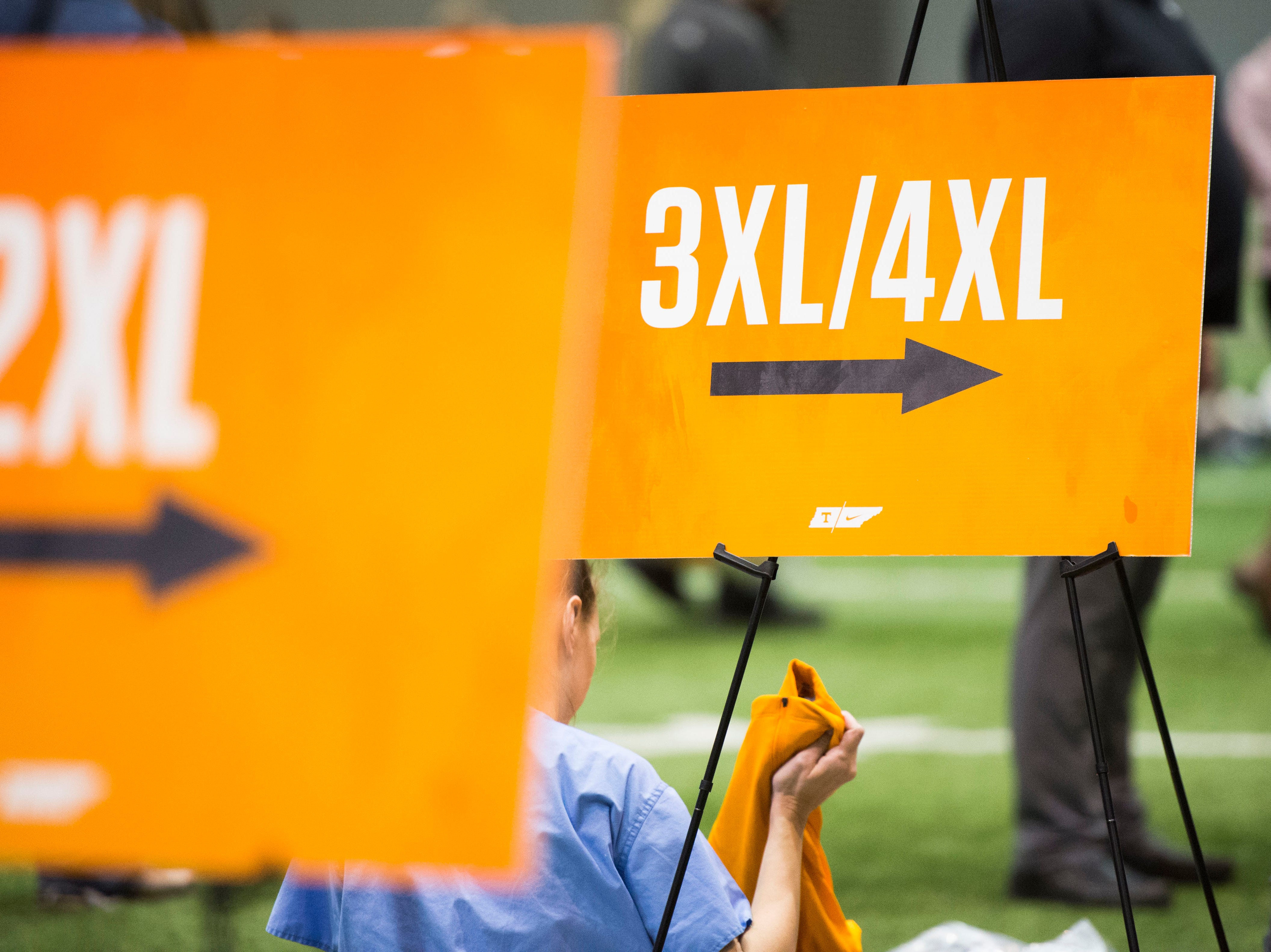 People shop for athletic apparel on Tennessee football's indoor practice field during University of Tennessee Athletic Department's inventory sale Wednesday, Dec. 12, 2018. Helmets and jerseys were sold along side the discount gear for hundreds of dollars.