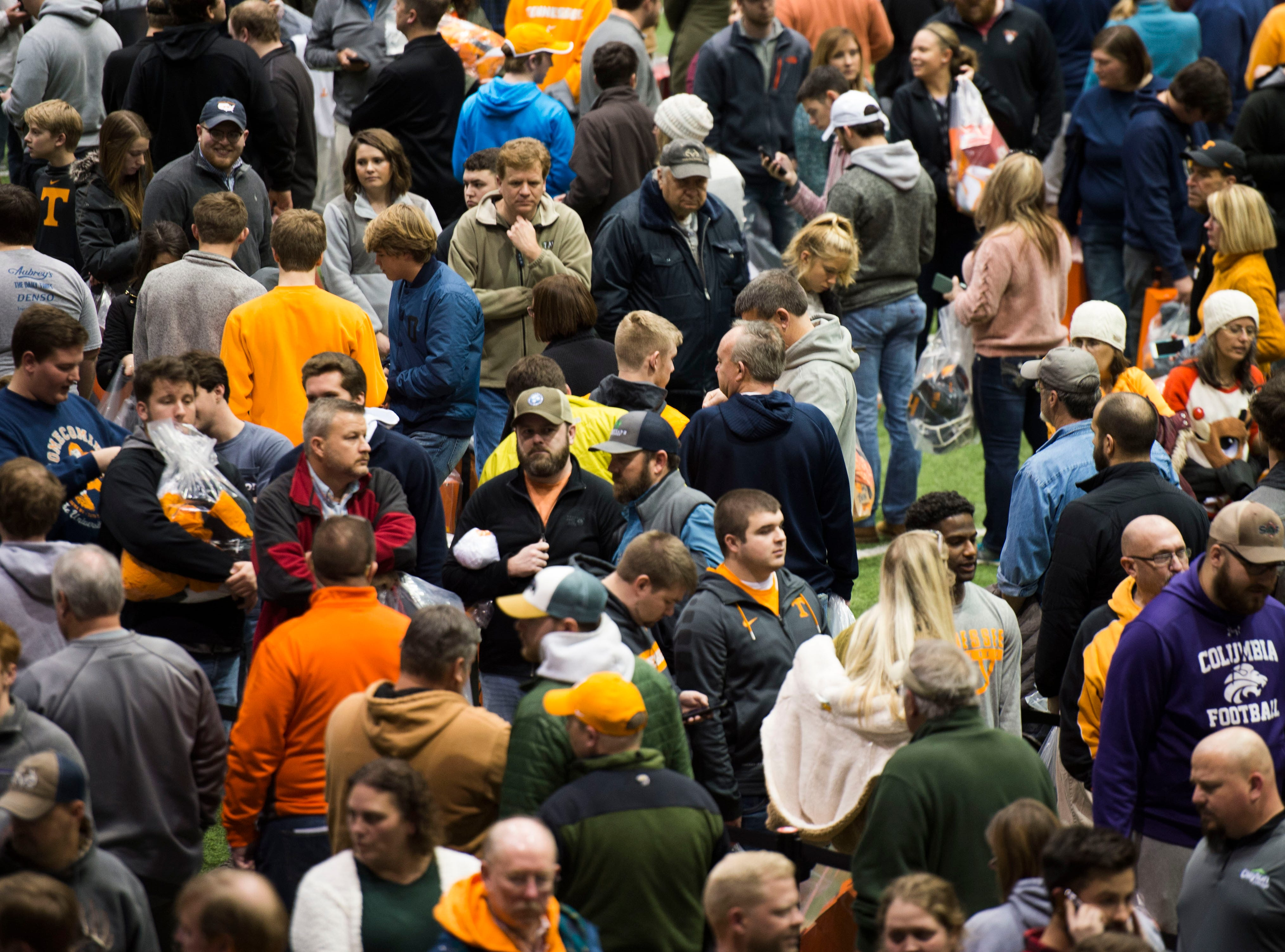 People wait in line to buy athletic apparel on Tennessee football's indoor practice field during University of Tennessee Athletic Department's inventory sale Wednesday, Dec. 12, 2018. Helmets and jerseys were sold along side the discount gear for hundreds of dollars.