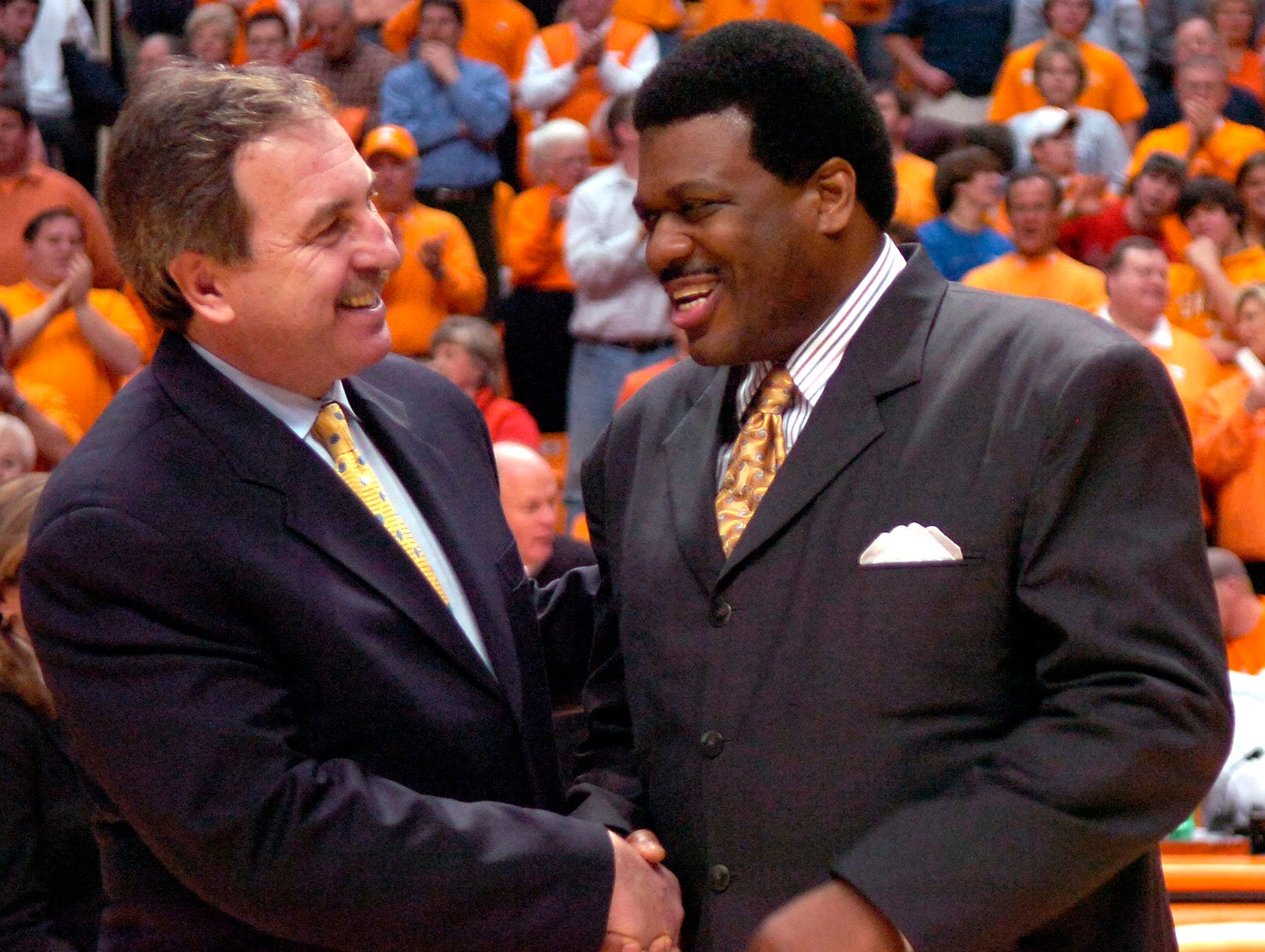 Former UT basketball great Bernard King (right) shakes hands with former teammate Ernie Grunfeld as he is recognized during the Kentucky game. King's #53 jersey was retired at halftime of the game.