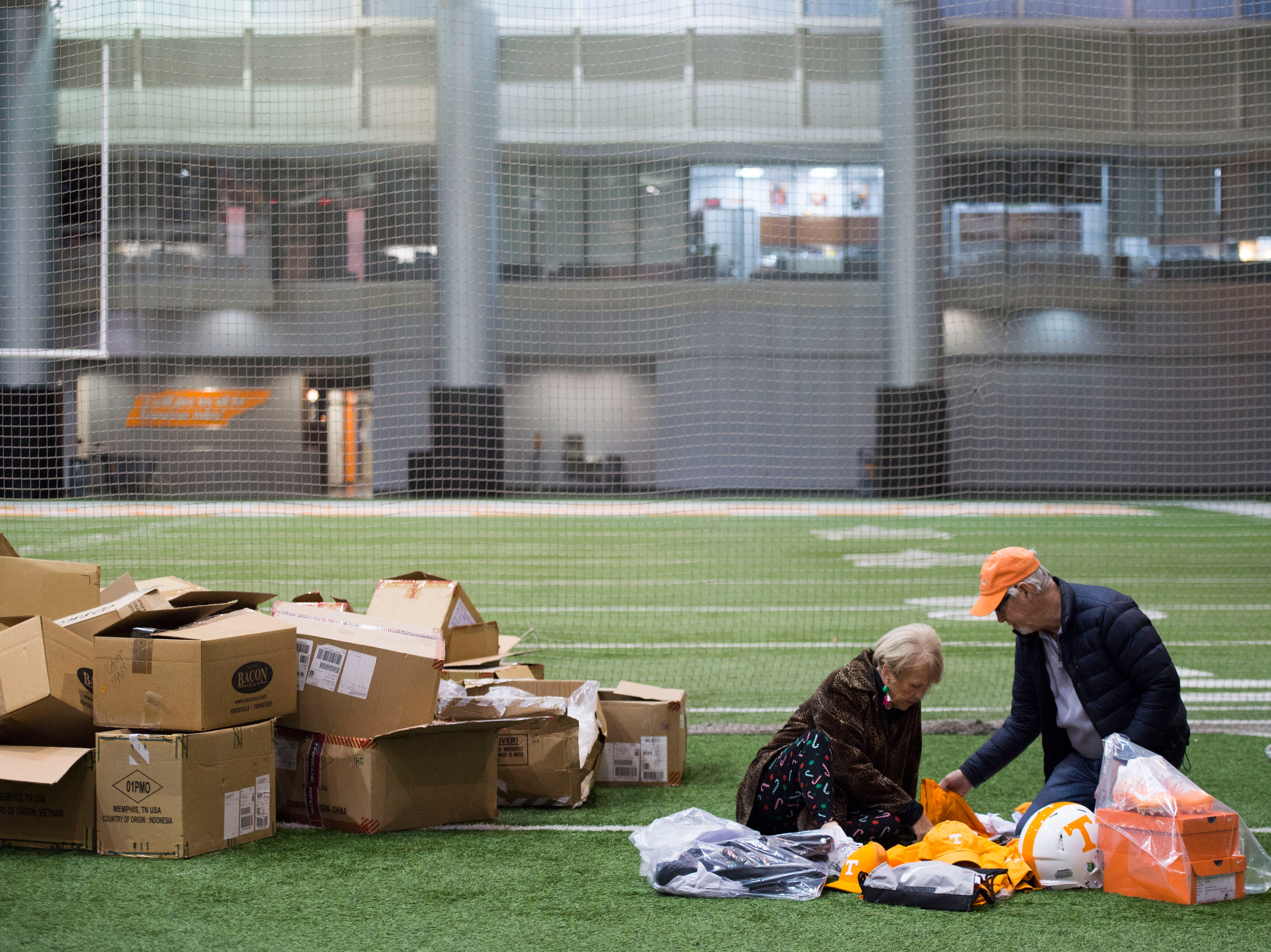 Carol Ann and Doyle Knight of Knoxville shop for athletic apparel on Tennessee football's indoor practice field during University of Tennessee Athletic Department's inventory sale Wednesday, Dec. 12, 2018. Helmets and jerseys were sold along side the discount gear for hundreds of dollars.