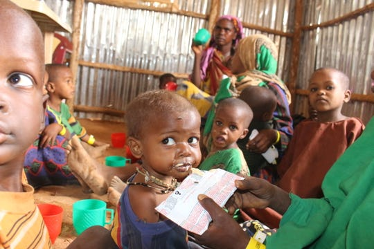 Children eat plumpy'nut therapeutic food at the MSF reception centre in Dolo Ado, Ethiopia. Many of the children from Somalia arrive malnourished.