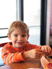 Three-year-old Bentley Cooper Middleton enjoys some curly fries and chocolate milk at the Arby's grand opening in Halls on Dec. 11.