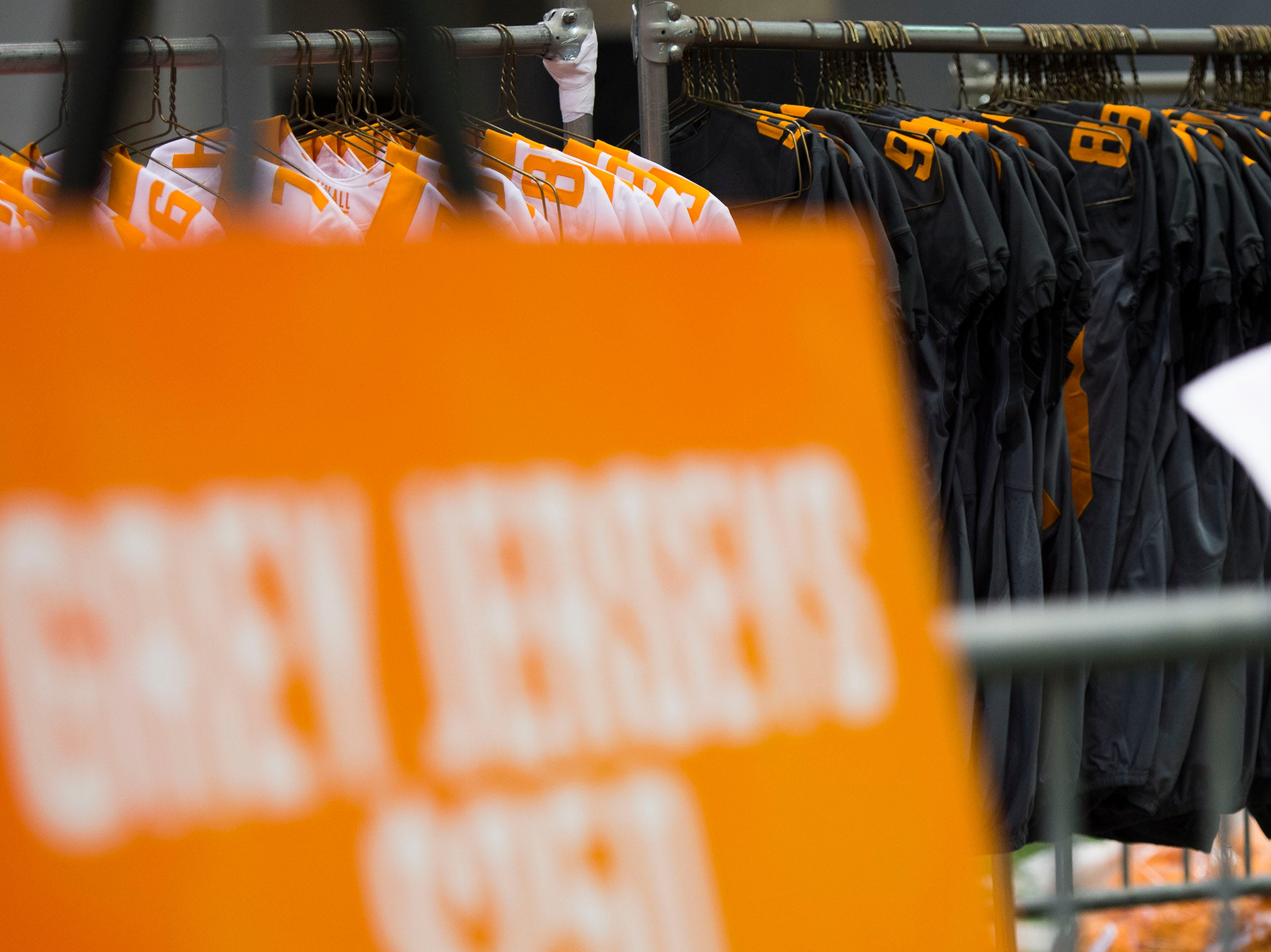 Jerseys hang for sale as people shop for athletic apparel on Tennessee football's indoor practice field during University of Tennessee Athletic Department's inventory sale Wednesday, Dec. 12, 2018. Helmets and jerseys were sold along side the discount gear for hundreds of dollars.