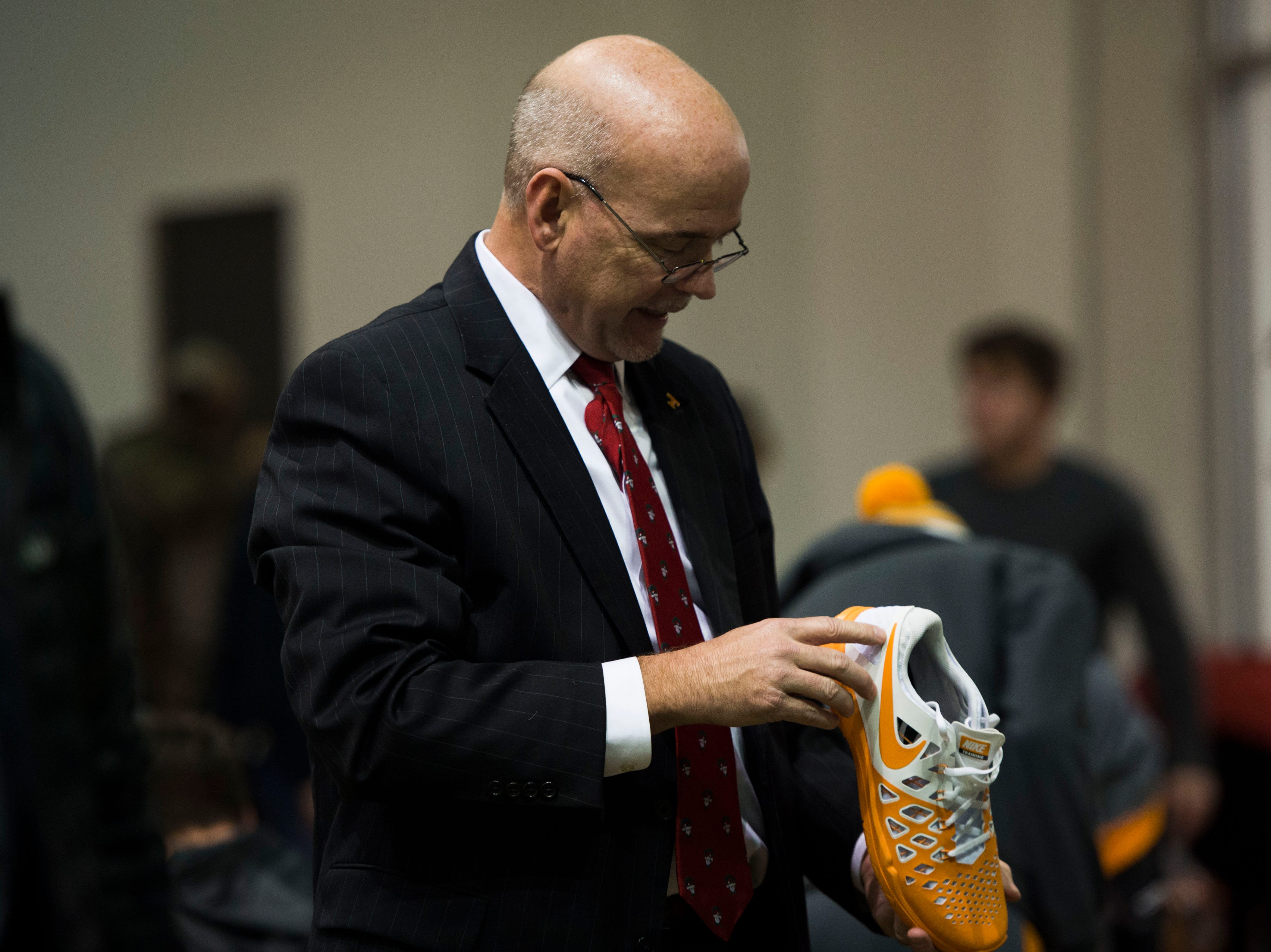 Joel Reeves, of Knoxville, looks at a pair of sneaks while shopping for athletic apparel on Tennessee football's indoor practice field during University of Tennessee Athletic Department's inventory sale Wednesday, Dec. 12, 2018. Helmets and jerseys were sold along side the discount gear for hundreds of dollars.