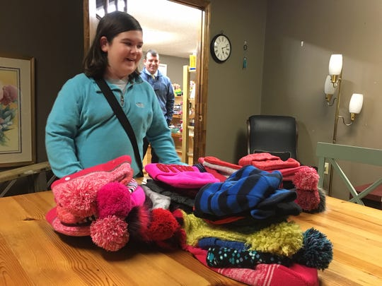 More hats and gloves! Ten-year-old Olivia Mason is all smiles as she looks at donated items in the community room at The Village Mercantile. In the background is proud dad Billy.