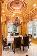 The formal dining area is done in shades of gold to add a luxurious setting.