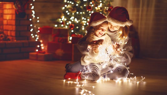 Merry Christmas Mother And Child Daughter With Glowing Garland Near Tree
