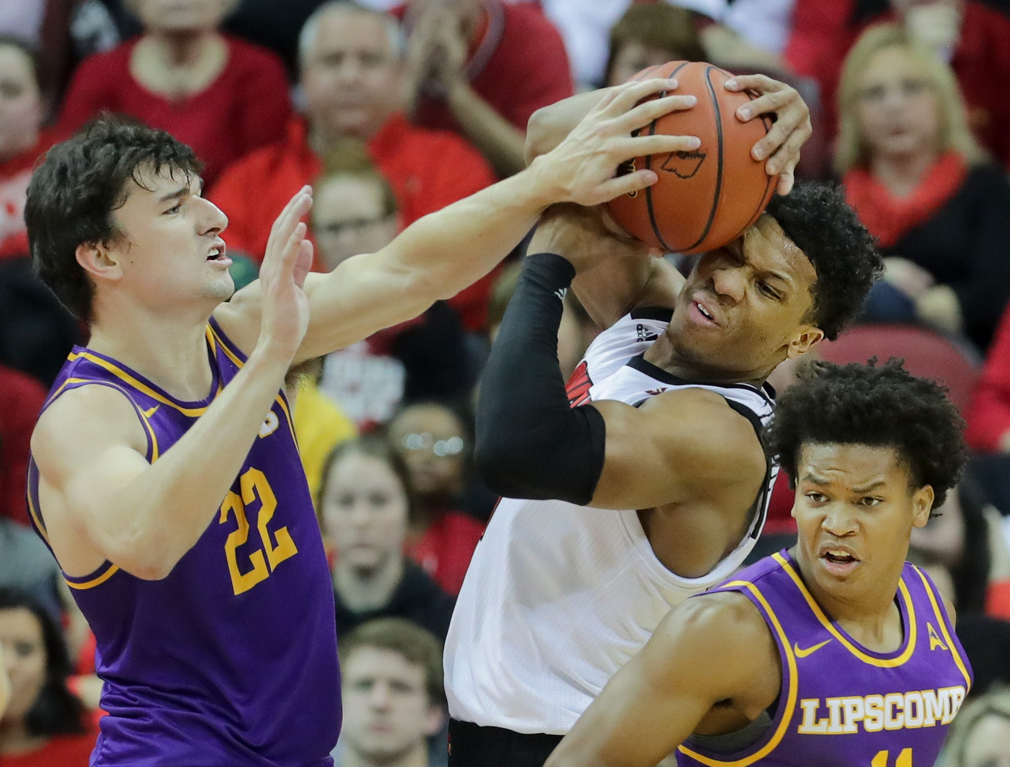 Louisville's Dwayne Sutton, center, fights for the ball with Lipscomb's Eli Pepper, left, and Alex Jones.  