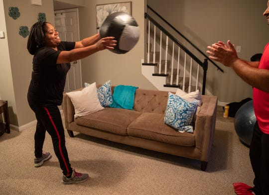 "Felicia Patterson works out with GymGuyz coach, Roy Elmore, Tuesday, Dec. 11, 2018 in Louisville Ky. ""They come to your house so it really helps with the motivation,"" Patterson said. ""You don't have to get ready to go out to the gym when its cold or raining."""