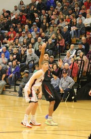 Dontaie Allen puts up a shot while a Roberston County defender stands in front of him.