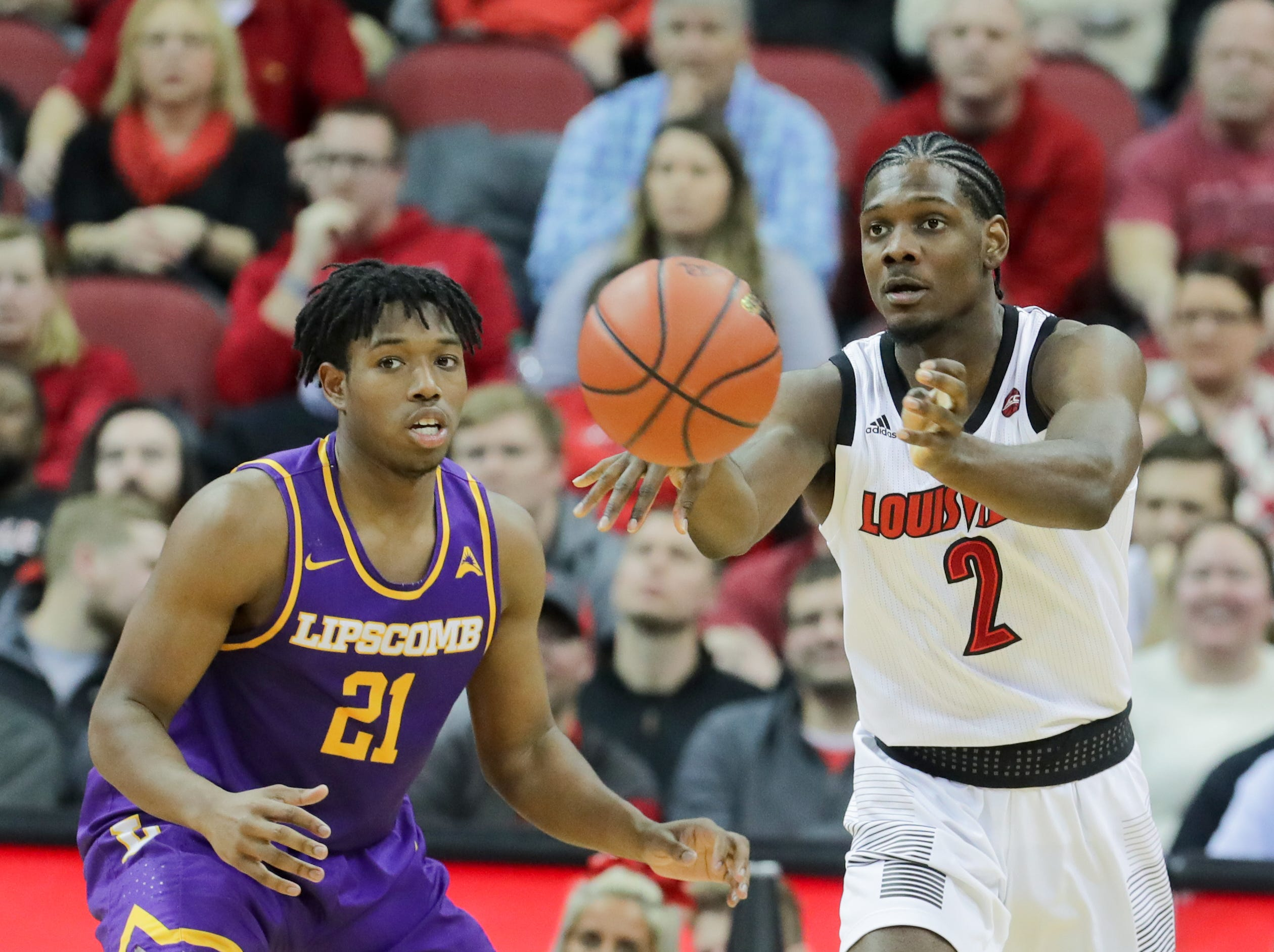 Louisville's Darius Perry passes while being guarded by Lipscomb's Kenny Cooper. 