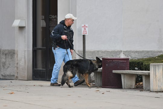 A member of the Lansing Police Department and his K-9 work in front of Veterans Memorial Courthouse in downtown Lansing Thursday, Dec. 13, 2018, after the building was evacuated due to a bomb threat.