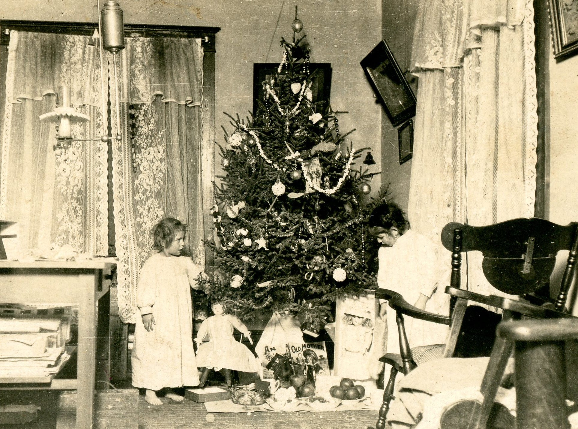 Two girls inspect what's under the Christmas tree, date unknown.