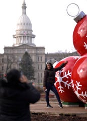 "Toni Harris of Detroit has her picture taken Thursday, Dec. 13, 2018, by co-worker Sharnita Mangum, of Troy in downtown Lansing.  ""I think they're pretty, Mangum said of the Christmas decorations at the roundabout at Michigan Avenue and Washington Square."