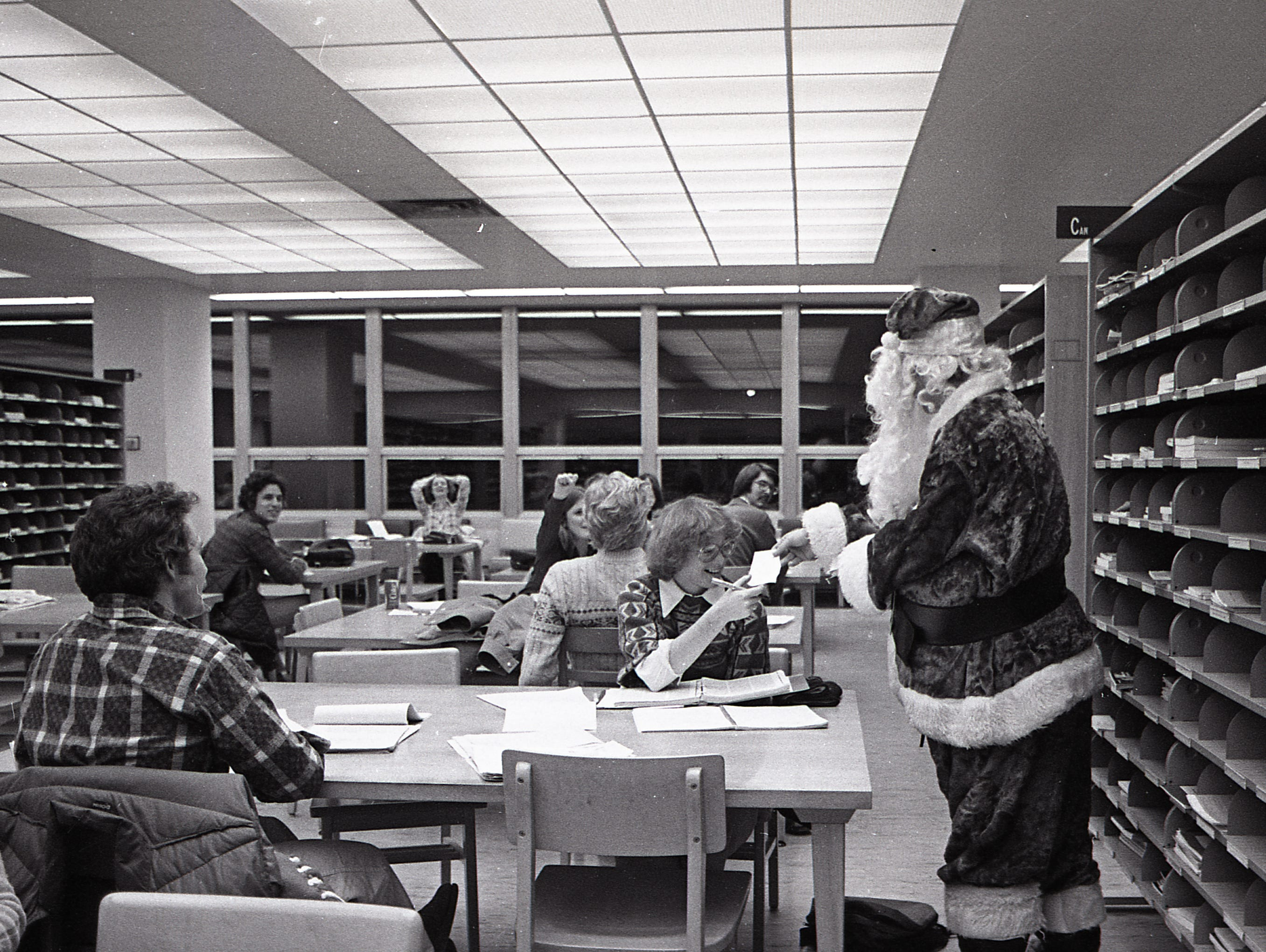 Santa hands out 4.0's to students studying at MSU's Main Library, Dec. 7, 1977.