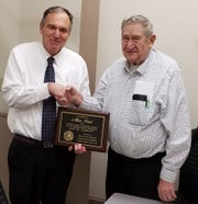 Manitowoc County Executive Bob Ziegelbauer (left) presents a plaque of appreciation for 13 years of service on the Manitowoc County Veterans Service Commission to Al Karl.