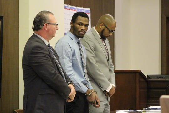 Lloyd Hinton Jr., 25, center, is flanked by his attorneys as the jury's verdict is read at his trial Wednesday. He was found guilty of attempted murder, a first-degree felony, and three other crimes in connection to a July shooting at Gotham City bar in downtown Marion.