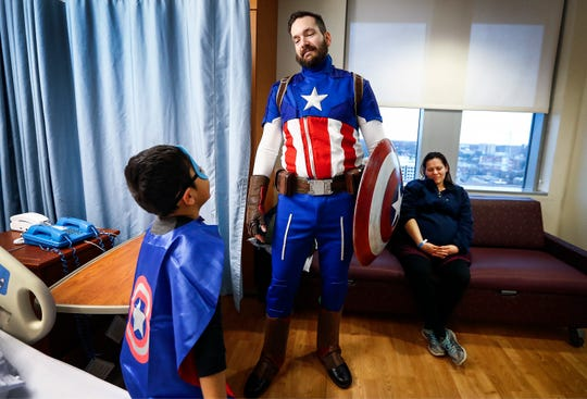 Dressed as superhero Captain America Jeremy Jones (middle) visits with Le Bonheur Children's Hospital patient Uriel Perez Almendarez, 7, (left) and his mother Mayra Almendarez. In January, Jones will be donating 60 percent of his liver to a former St. Jude Research Hospital employee.