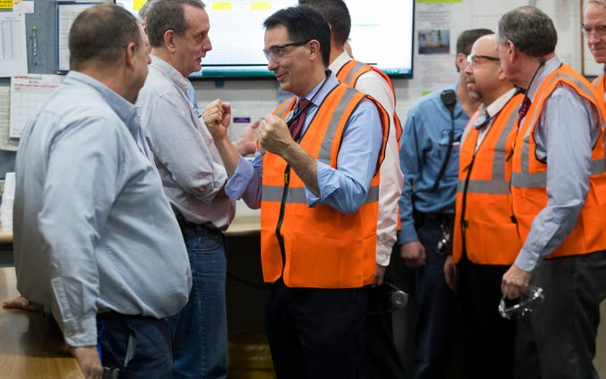 Gov. Scott Walker (center) talks with workers Thursday at Kimberly-Clark's Cold Spring plant in Neenah. Taxpayers will pay the Fox Valley company up to $28 million over five years under a deal struck by Walker to keep the plant open and jobs in the state.