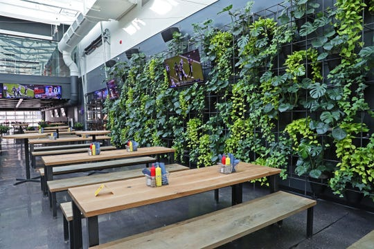 Beyond Glass + Griddle's dining room and its standard tables is beer-hall-style seating and a wall of plants.